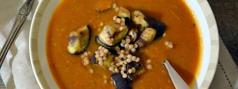Eggplant and tomato couscous soup in a white bowl with a spoon in it